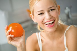 Young happy smiling woman with tomato at kitchen
